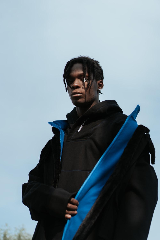 man in black top holding bluejacket