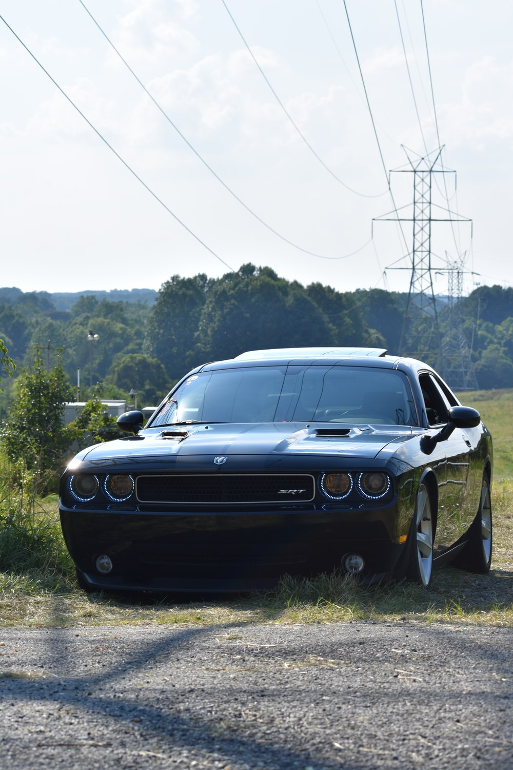black coupe parked near grass field during daytime