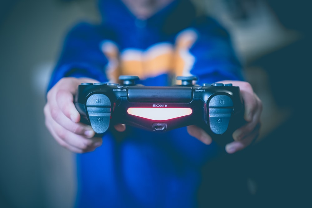 person holding black wireless controller