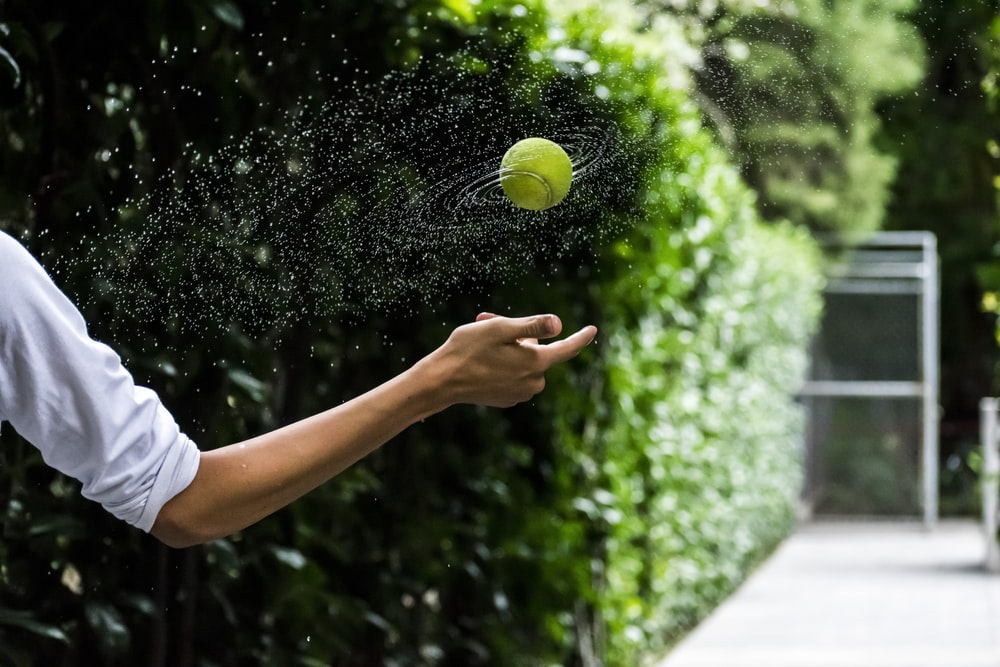 person throwing tennis ball