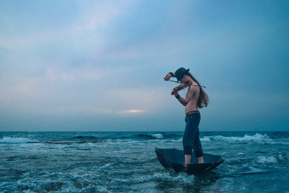 person wearing blue jeans riding boat playing violin