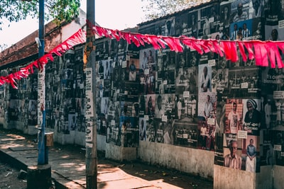 photography of assorted photos on concrete wall during daytime