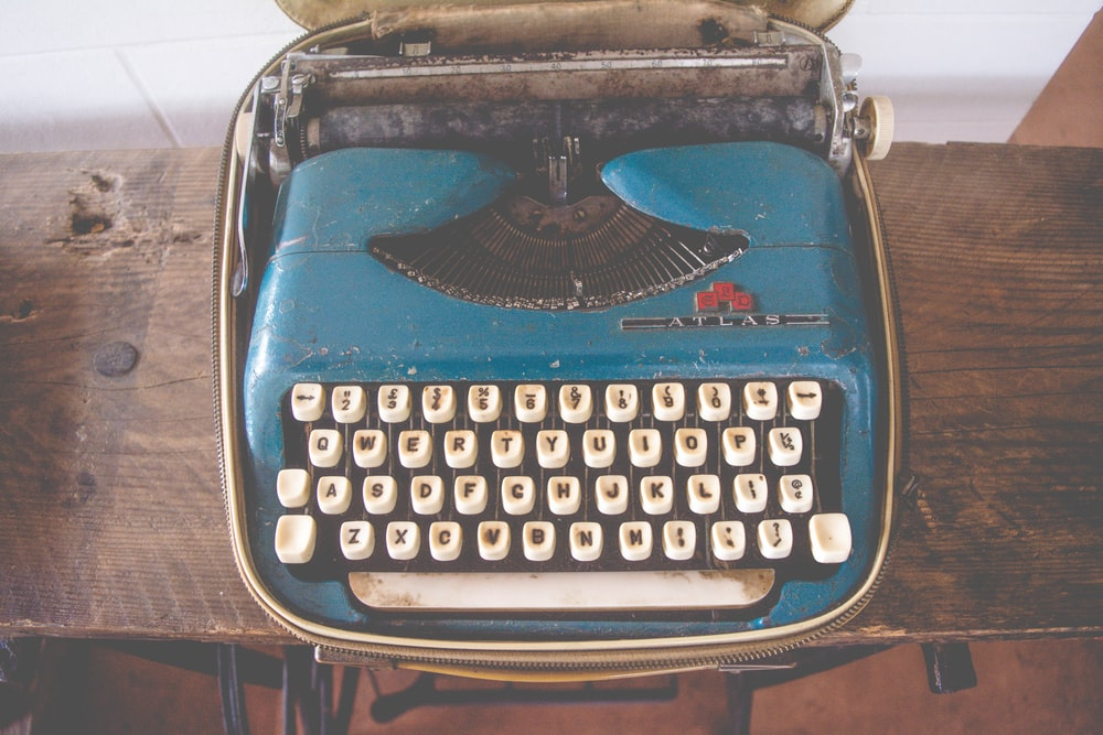 blue and white typewriter on brown wooden consoel