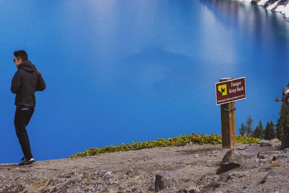 man walking away from danger keep away signage by the blue lake