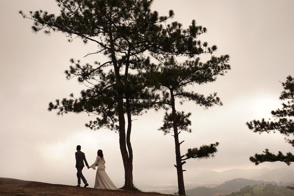 man and woman walking near tall tree