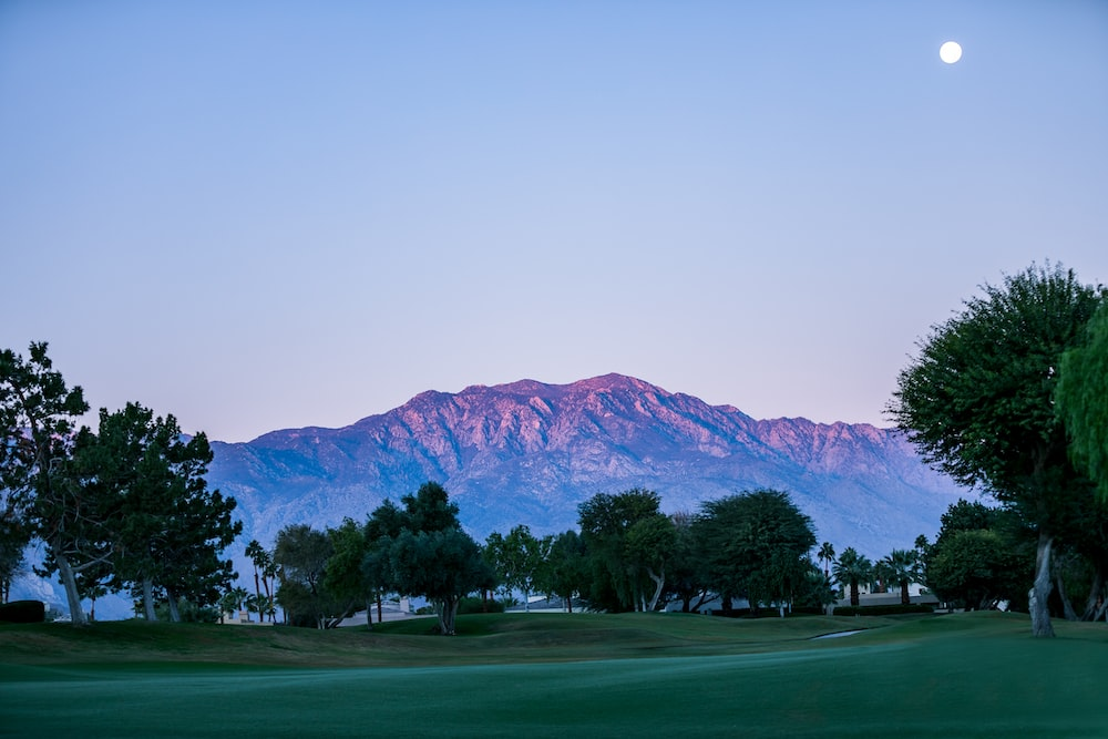 moon above mountain and golf course