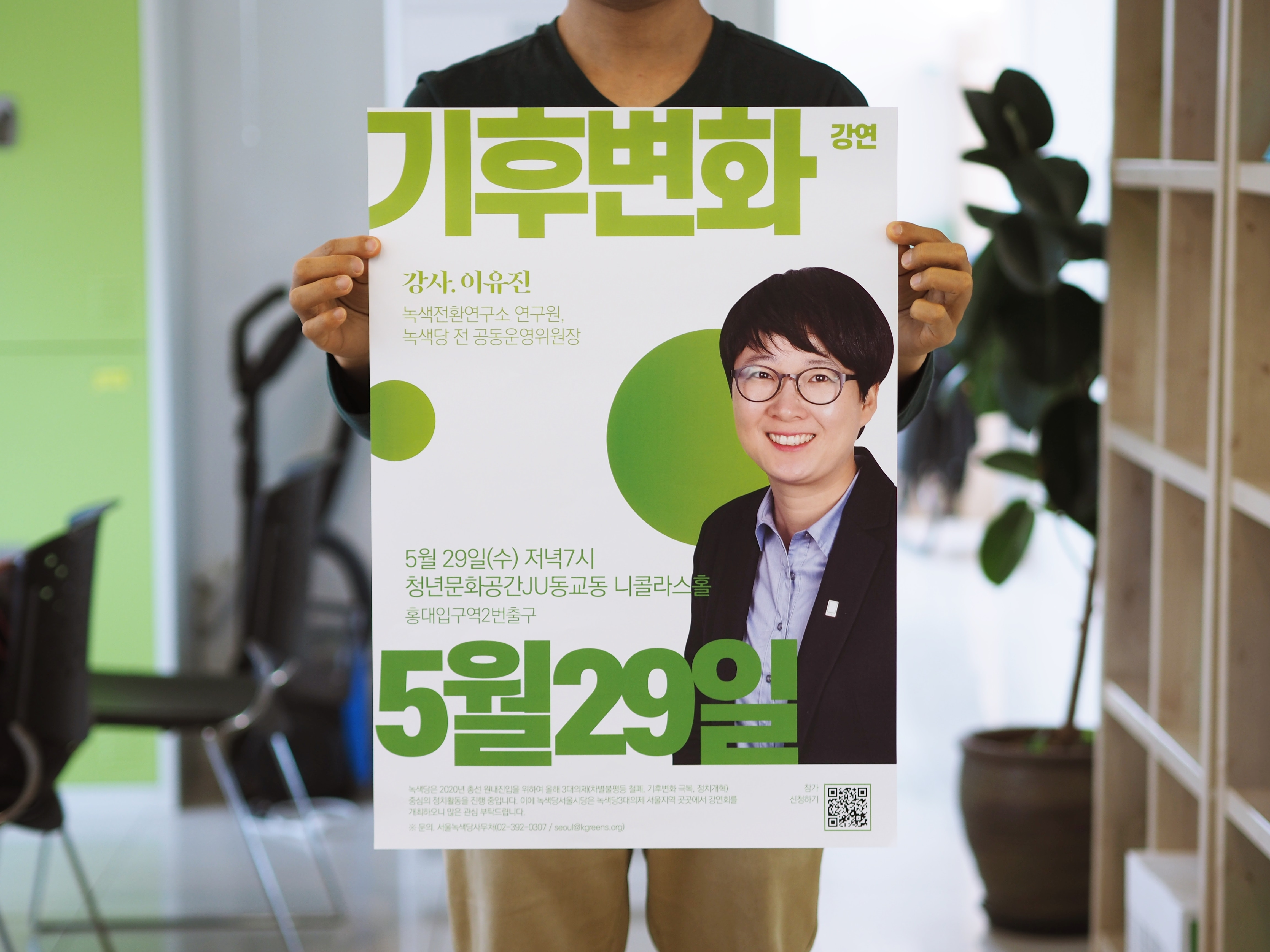 standing person holding poster with smiling man photo and Hangul texts