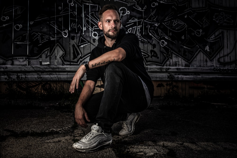 man sitting on ground near art wall