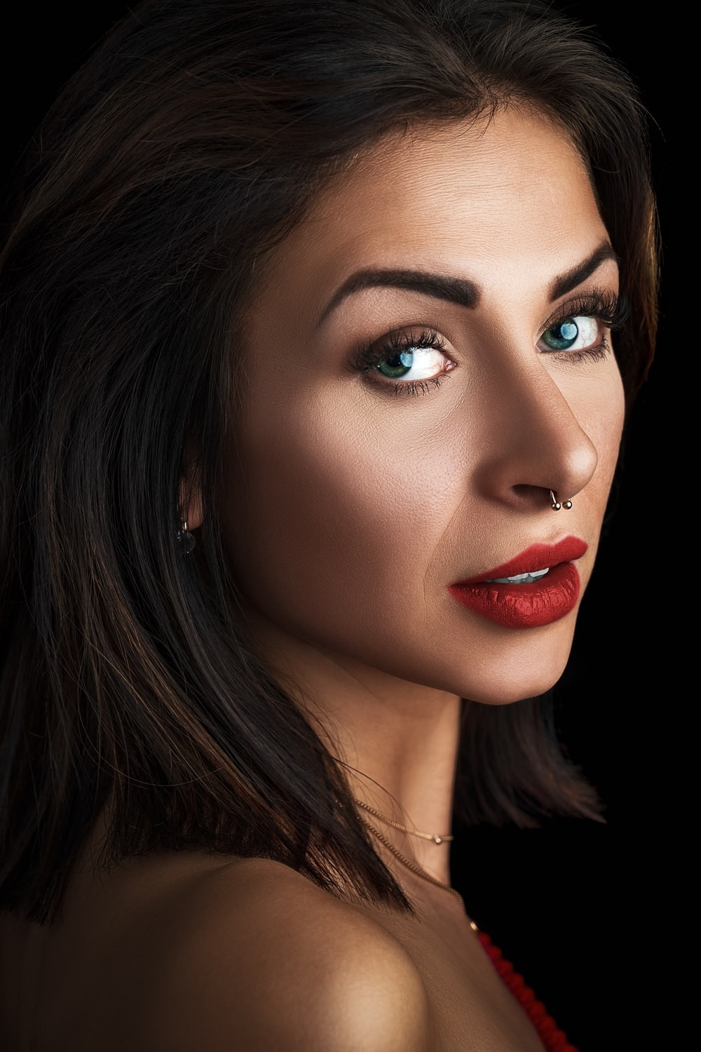 woman wearing red lipstick with piercing on nose