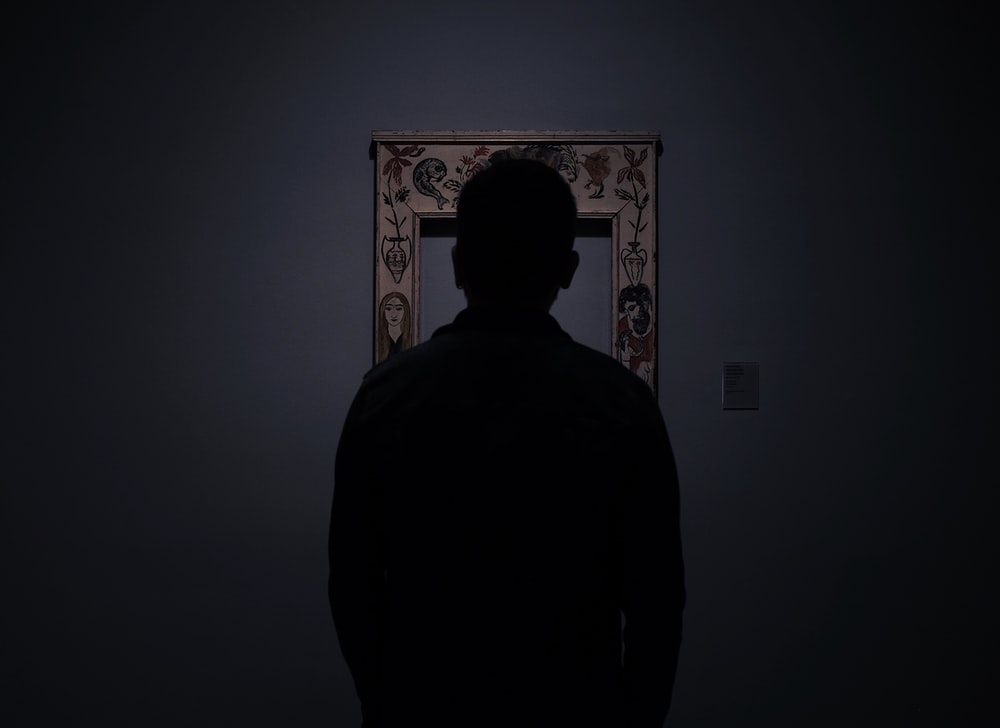 silhouette of person facing an empty photo frame