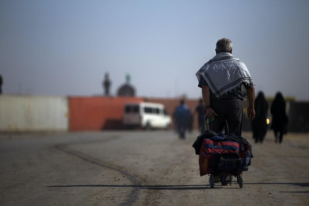 man walking while pulling wheeled bag