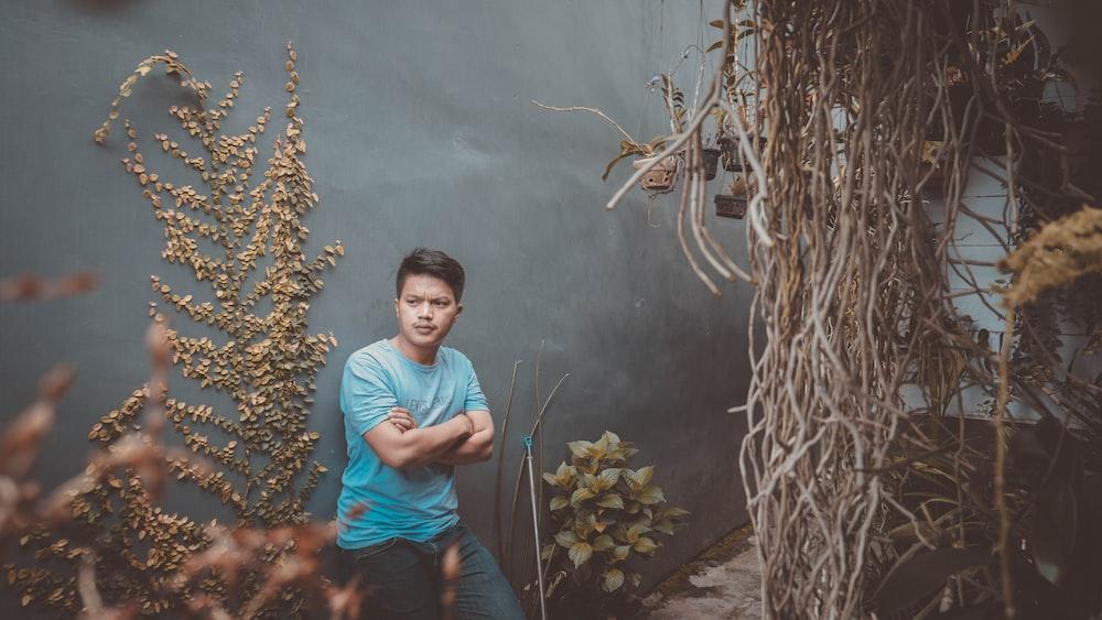 man in blue shirt near plants