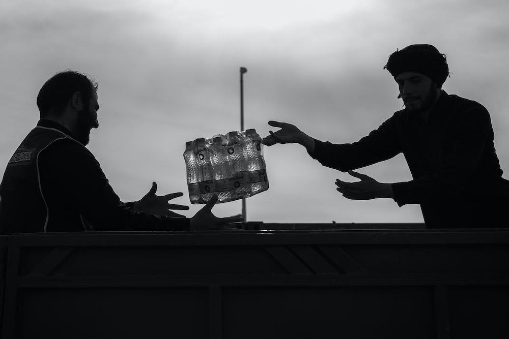 man catching water bottles from man