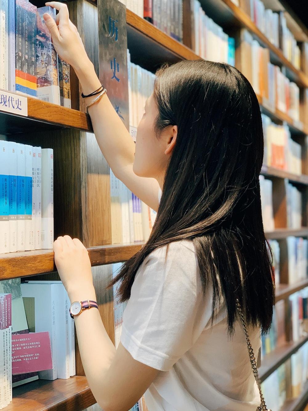 woman wearing white crew-neck shirt picking on book