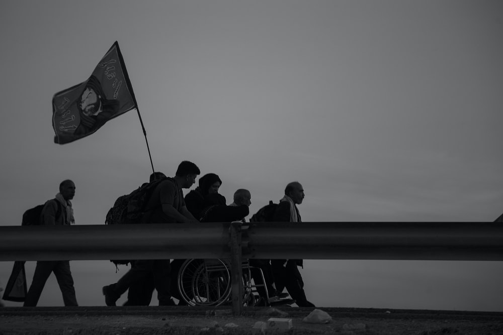 grayscale photo of people walking on street while holding flag