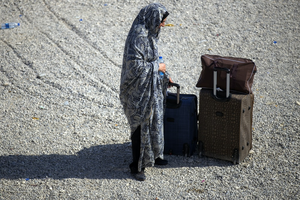 woman standing beside two luggage during daytime
