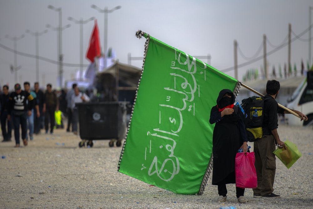 man and woman carrying green flag