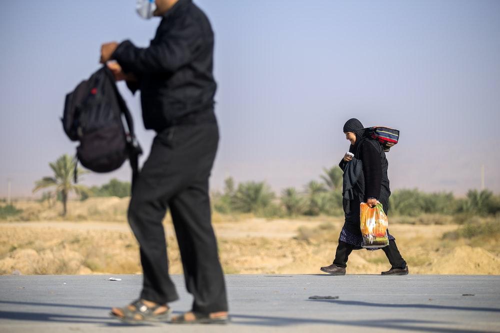 man wearing black jacket holding backpack