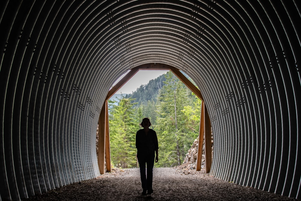 silhouette of person under tunnel