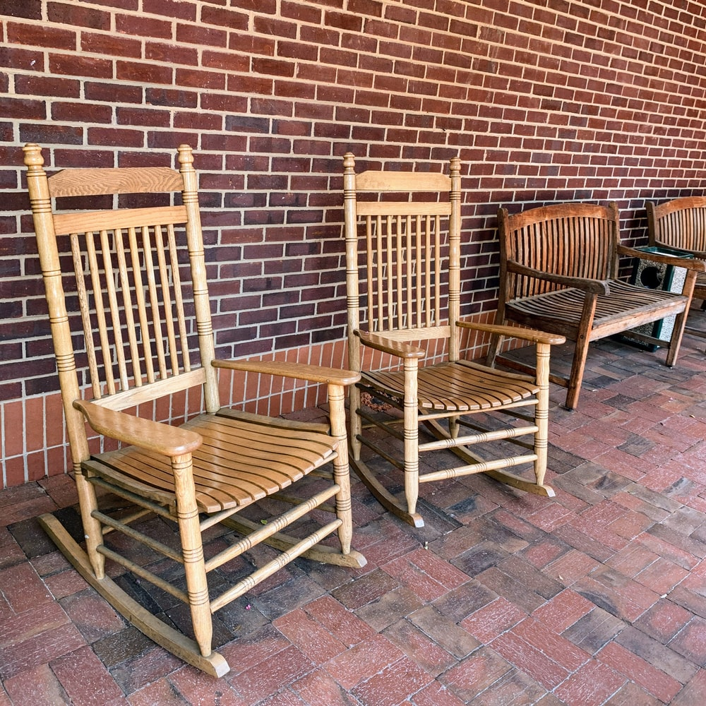 two brown wooden rocking armchairs
