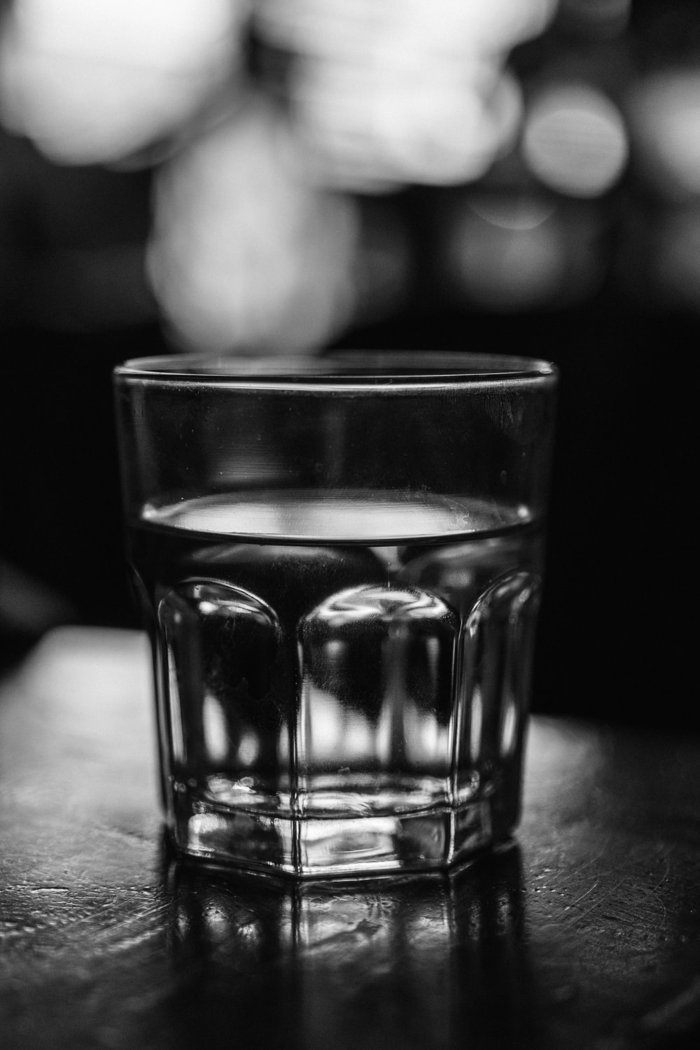 grayscale photo of a drinking glass with water