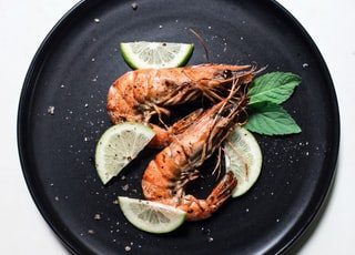 cooked shrimp with sliced of lime and basil