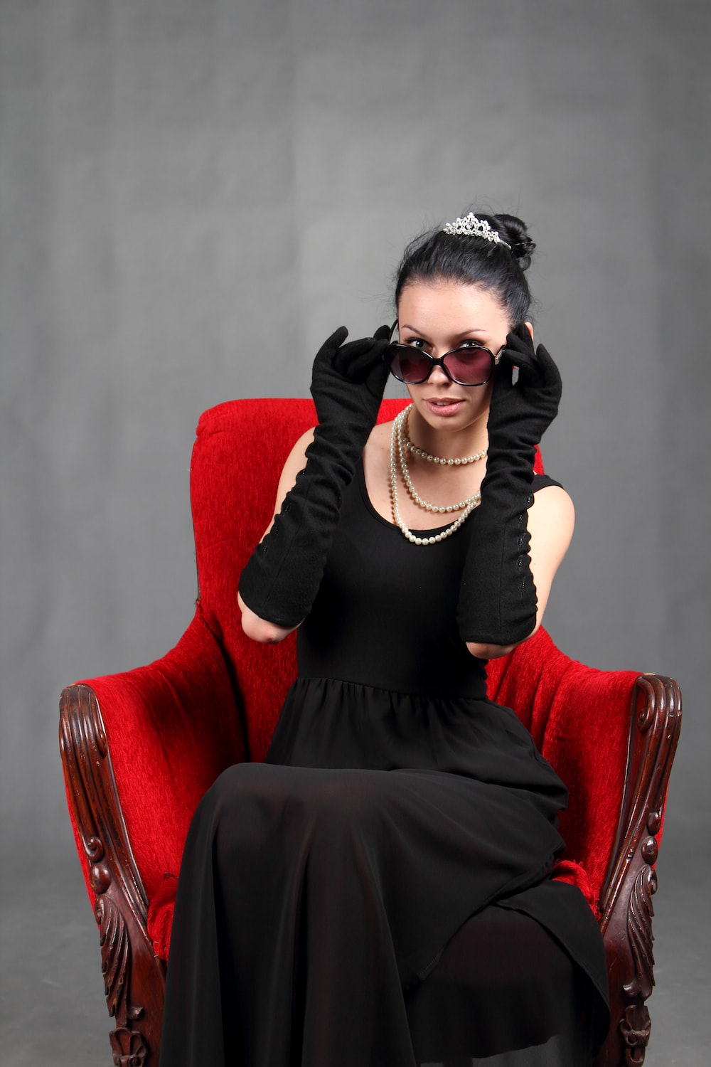 woman wearing black dress sitting on chair