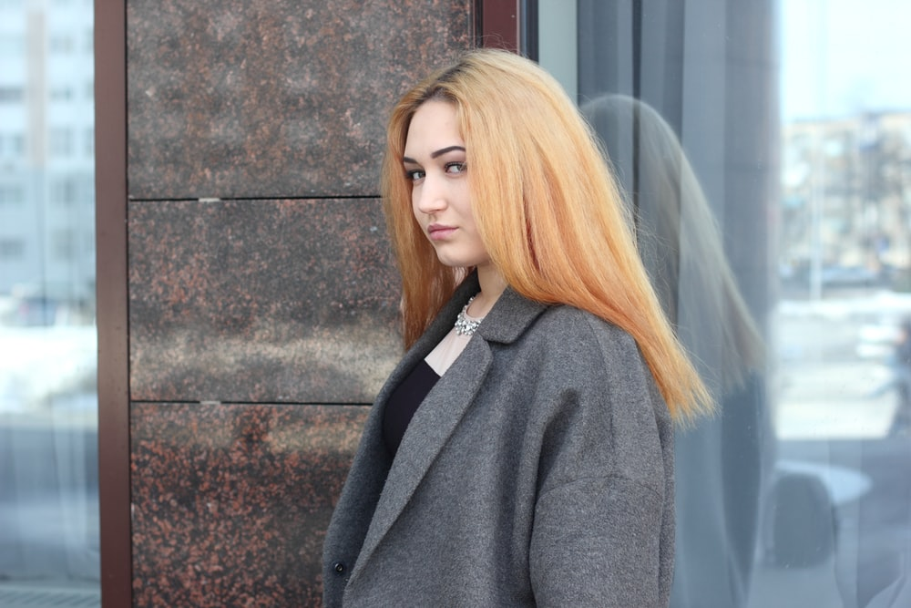 woman in gray suit jacket near glass wall