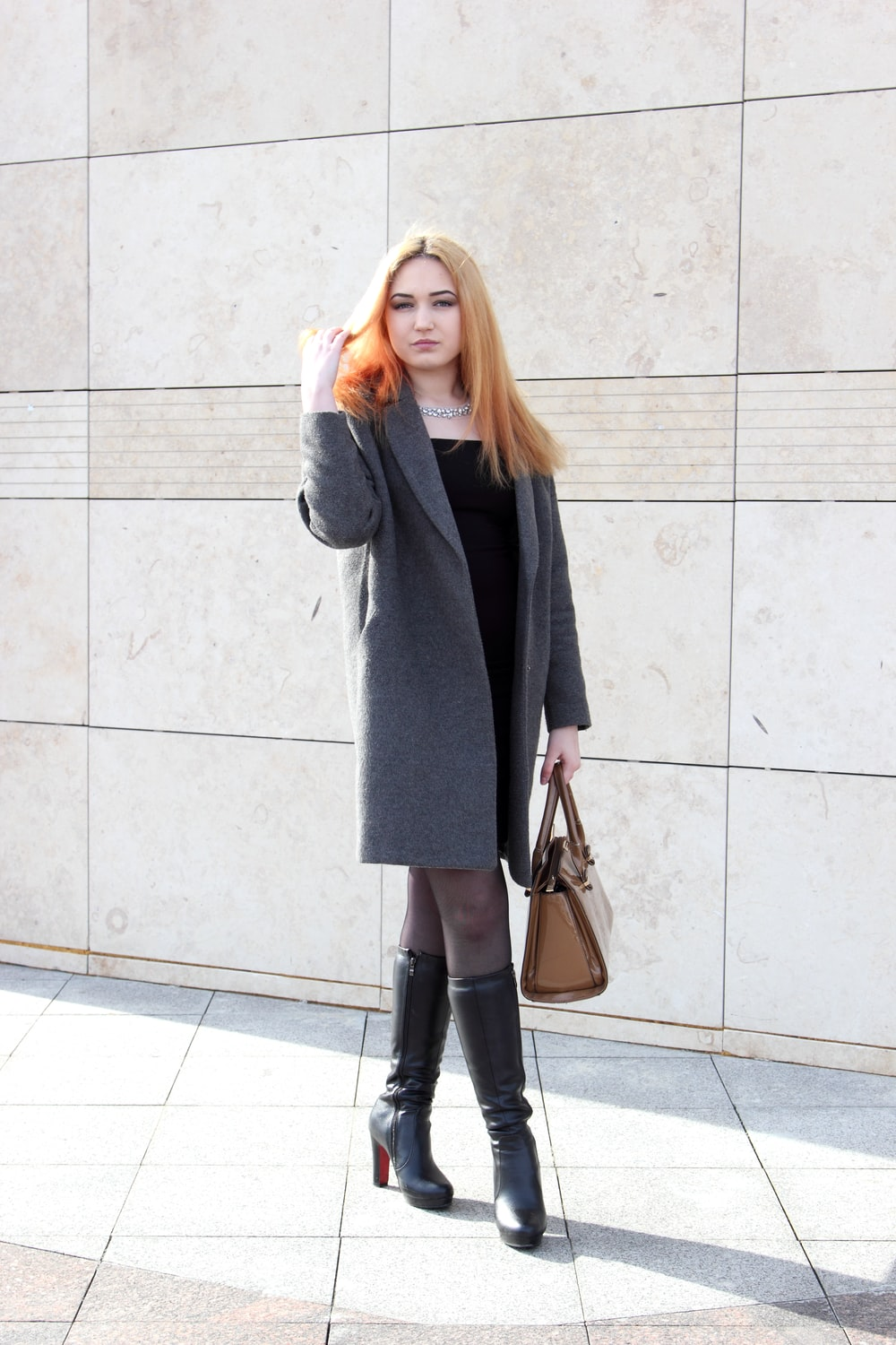 woman standing beside wall while holding her hair during daytime