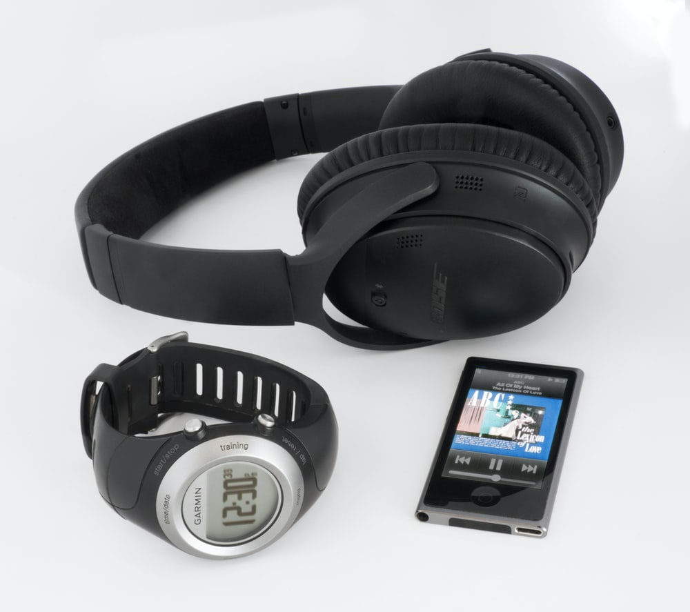 black Bose wireless headphones near smartwatch and iPod