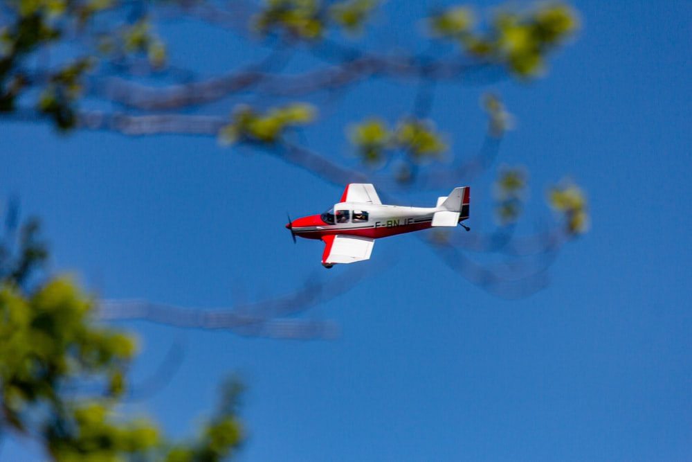 photography of white and red biplane during flight during daytime