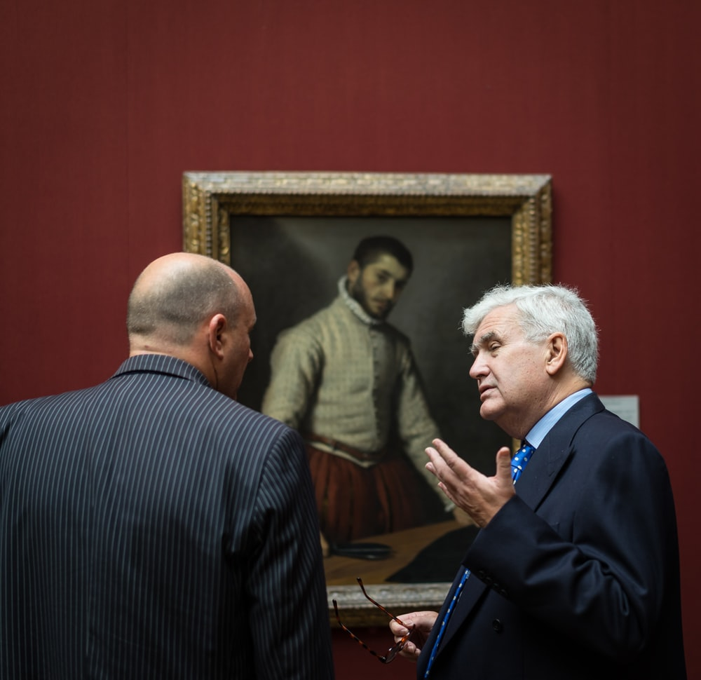 two men standing beside painting