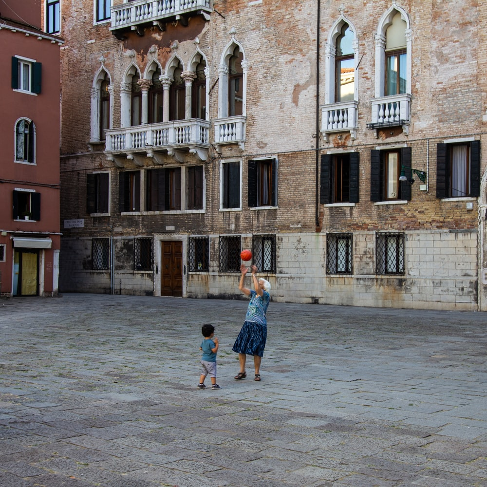 woman playing with child using basketball