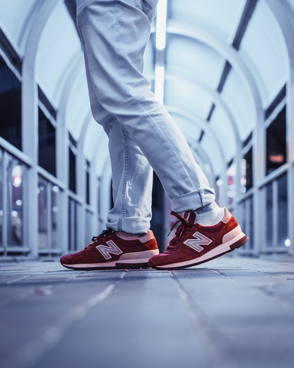 person wearing pair of red New Balance low-top sneakers