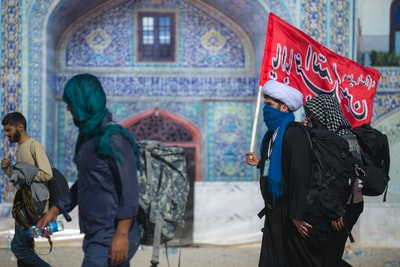 person carrying red flag iranian teams background