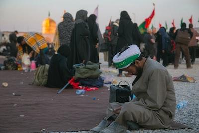 man sitting on ground wearing gray thobe dress iranian teams background