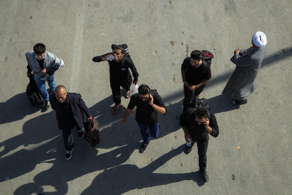 group of men walking on pavement