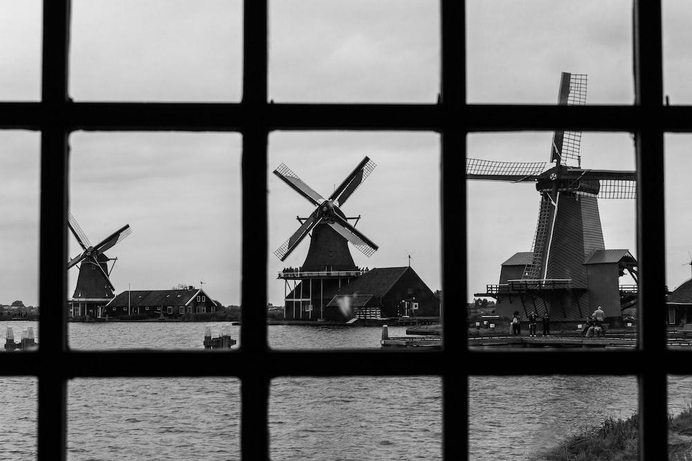 grayscale photo of windmill near body of water
