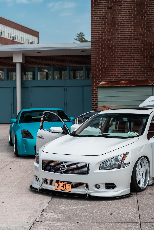 white Nissan car besides blue car