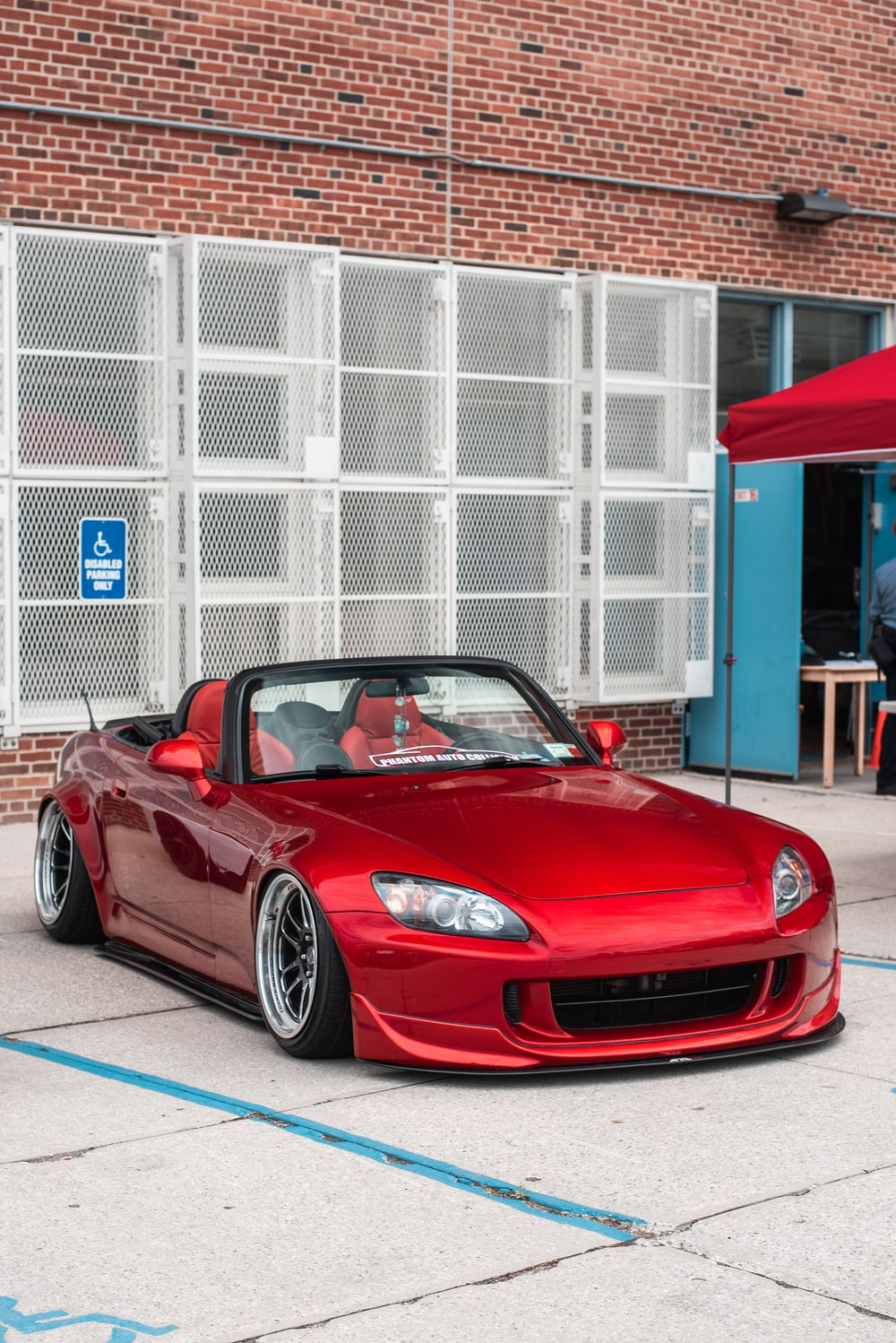 red convertible coupe on gray pathway