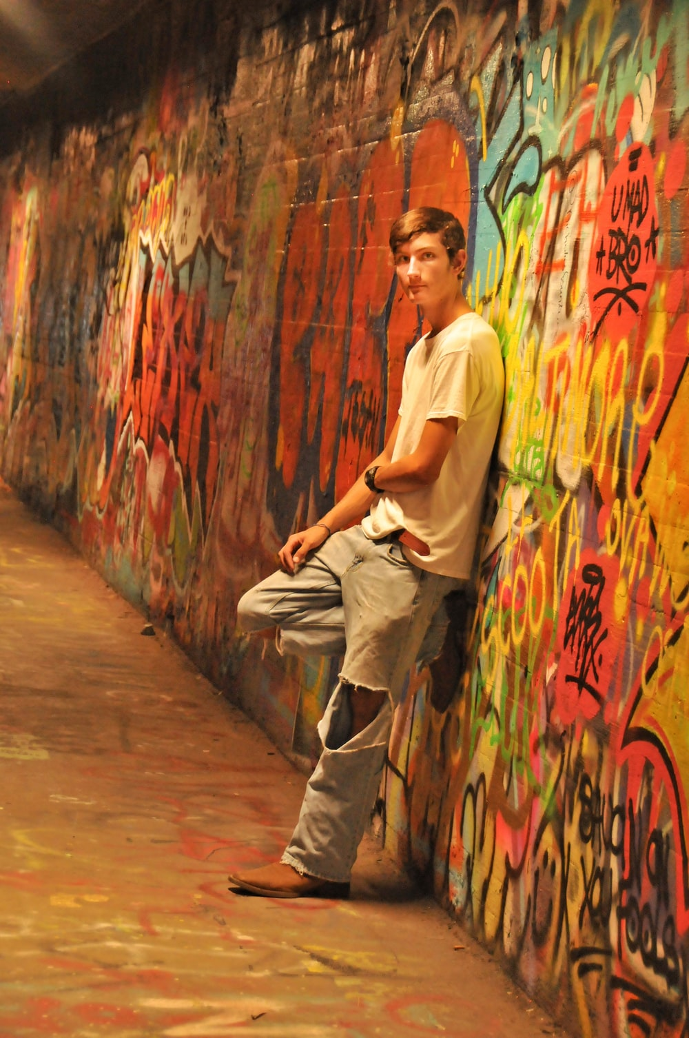 man looking at his left leaning backwards on wall with mural