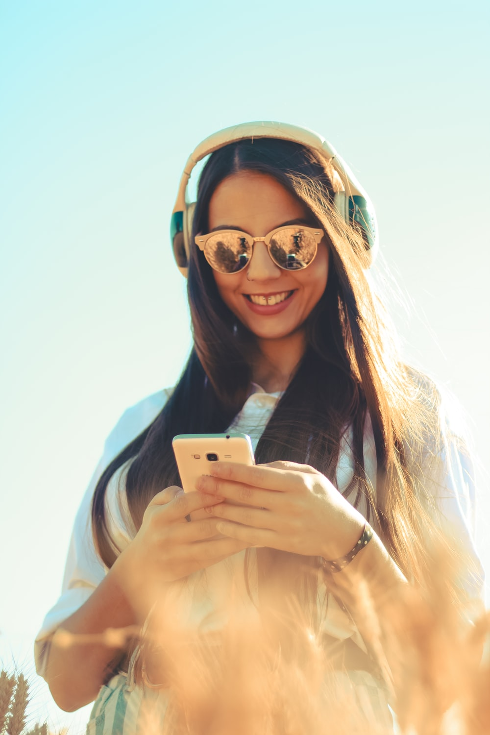 woman standing and smiling while using phone