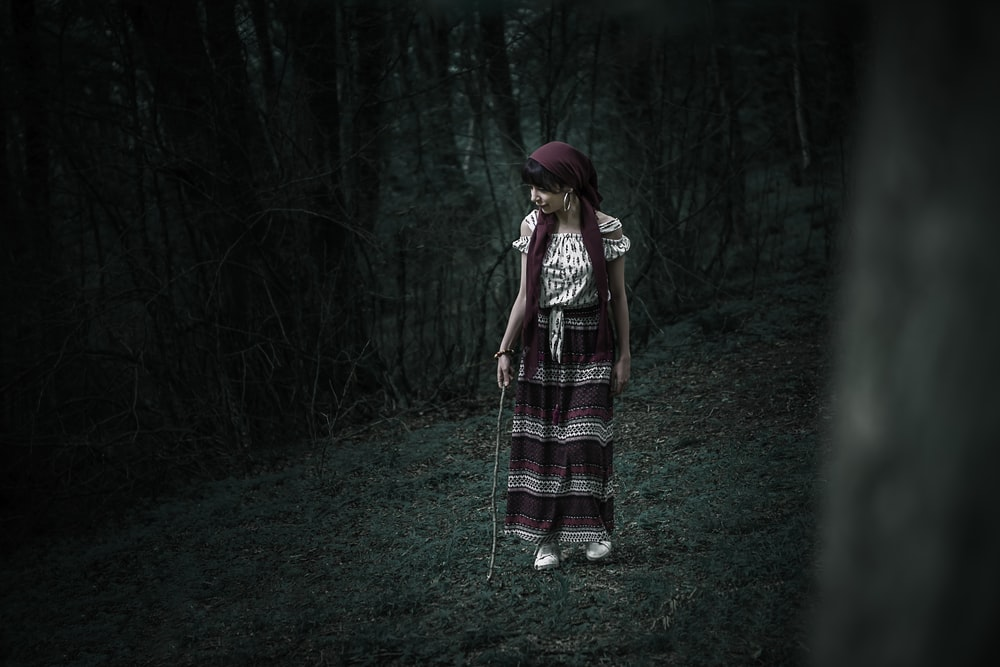 woman in white and maroon dress standing in the forest