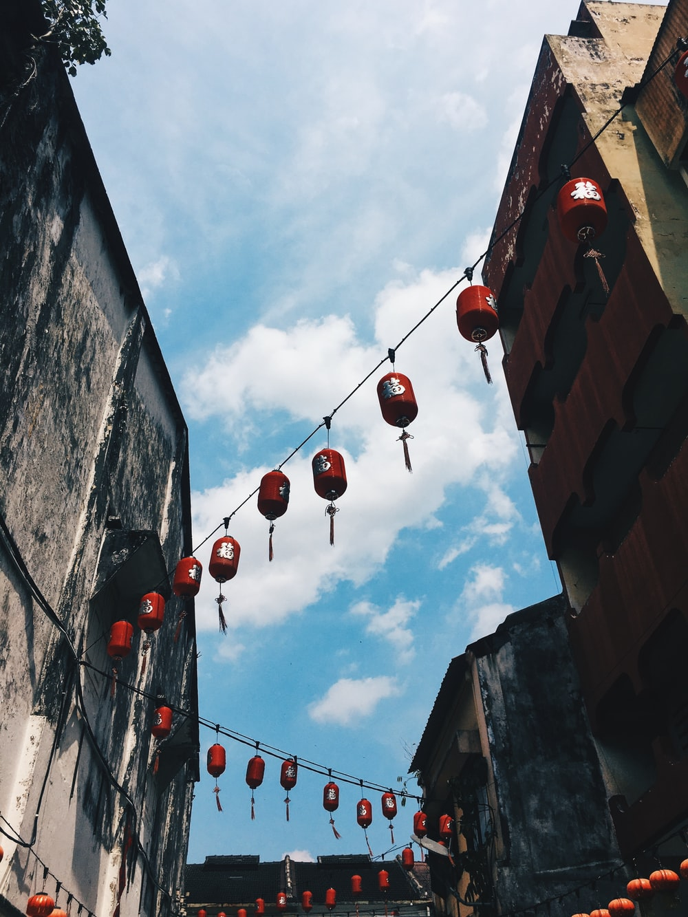 low-angle photography of Chinese lanterns hanging between buildings