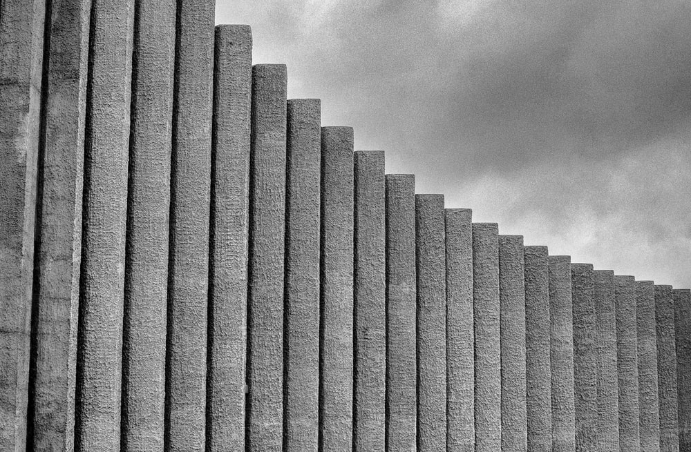 grayscale photography of concrete wall under cloudy sky