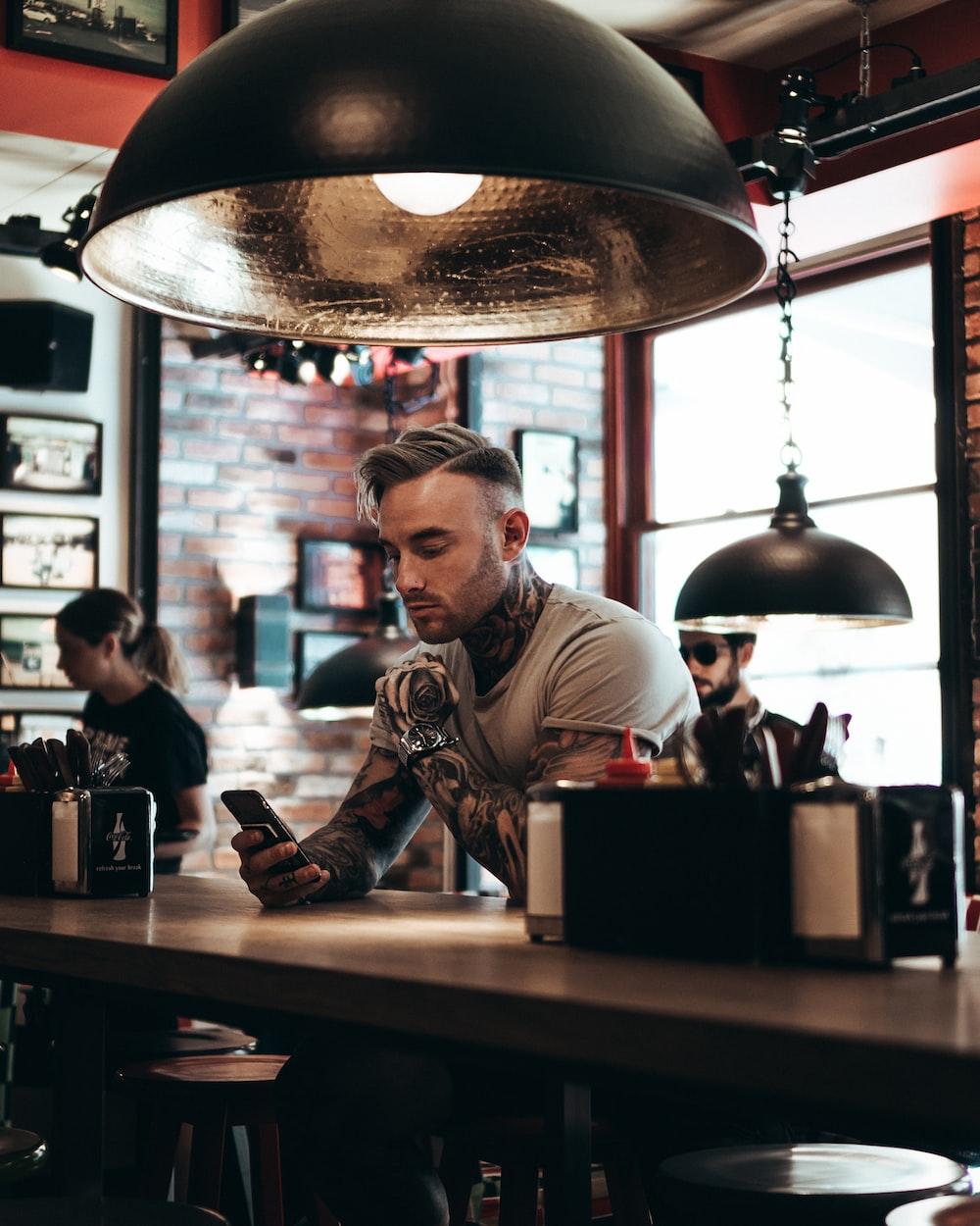 man sitting beside bar counter
