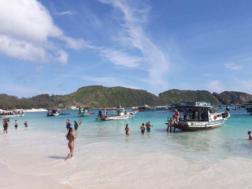 people on white sand beach during daytime