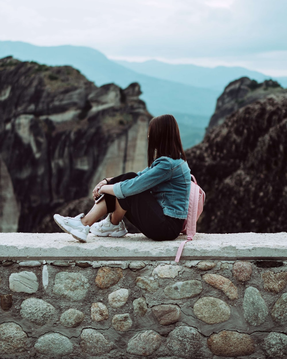 woman sitting on top of brick wall facing the mountains