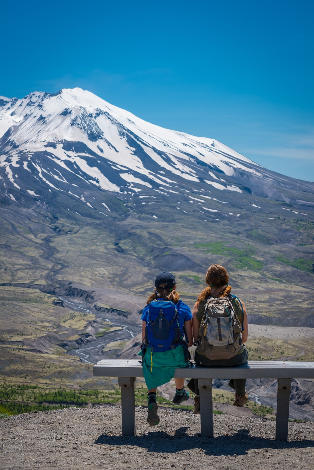 two people sitting on bench facing mountain
