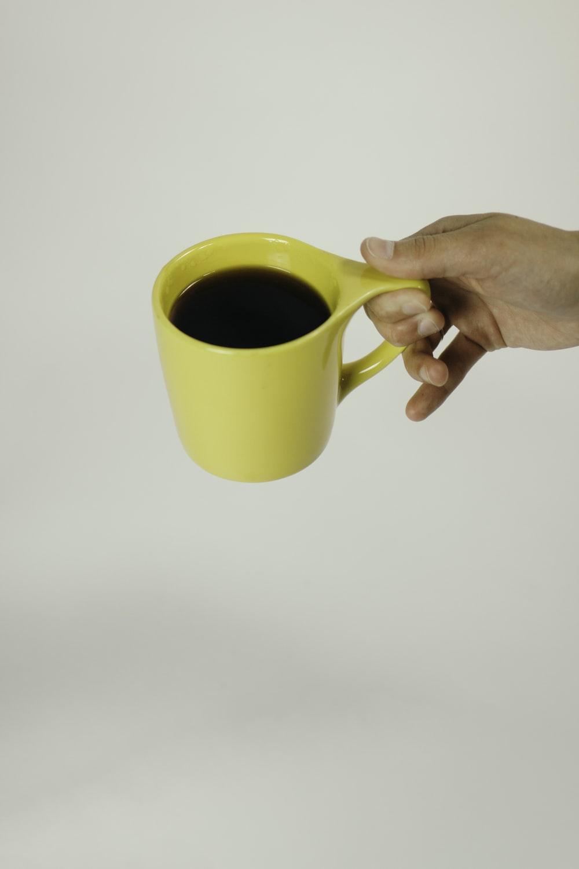 black beverage filled yellow mug